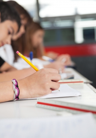 high school students: High school students writing at desk in classroom