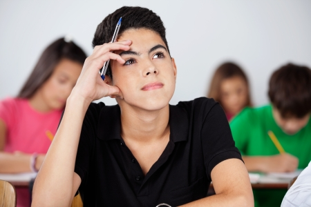 schoolwork: Thoughtful teenage boy looking up while sitting in classroom