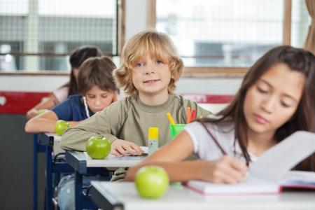 niños escribiendo: Retrato del pequeño colegial lindo que se sienta en una fila con sus compañeros de clase en el aula