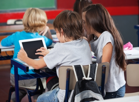 child school: Rear view of little schoolchildren using digital tablet at desk in classroom
