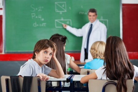 Portrait of young schoolboy leaning at desk with teacher teaching in background photo