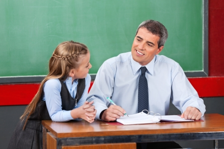 Mature male teacher looking at schoolgirl against chalkboard in classroom Stock Photo - 23747586