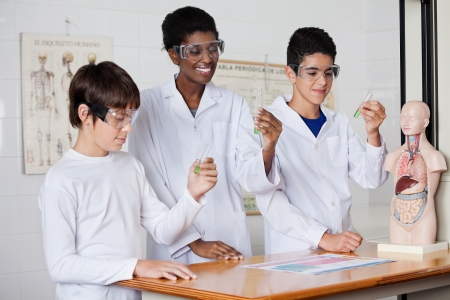 Young teacher with students examining chemical solution in test tube at desk in lab photo