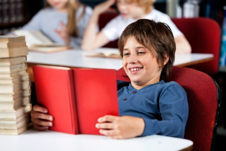 Relaxed little schoolboy smiling while reading book at table in library with classmates in background Stock Photo - 23747642