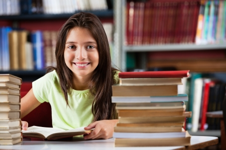child studying: Portrait of cute schoolgirl smiling while sitting with stack of books at table in library Stock Photo