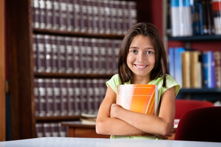 Portrait of cute little schoolgirl holding book while sitting at table in library Stock Photo - 23747666