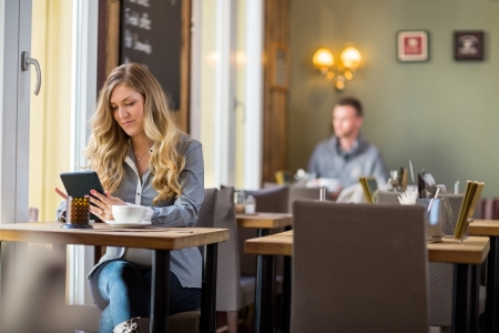 women coffee: Young pregnant woman using digital tablet at table with man sitting in background Stock Photo