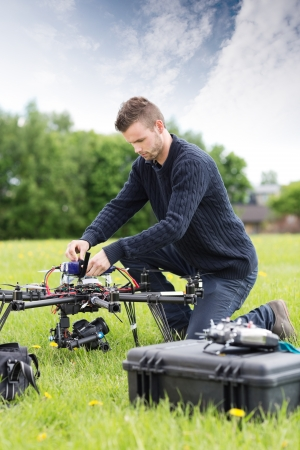 Young engineer assembling UAV helicopter in park photo
