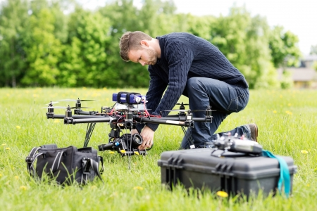 Young engineer setting SLR camera on UAV helicopter at park photo