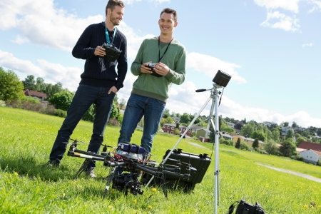 remote controls: Happy young technicians holding remote controls of UAV helicopter at park Stock Photo