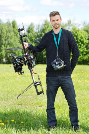 Portrait of confident technician standing with UAV helicopter and remote control in park photo