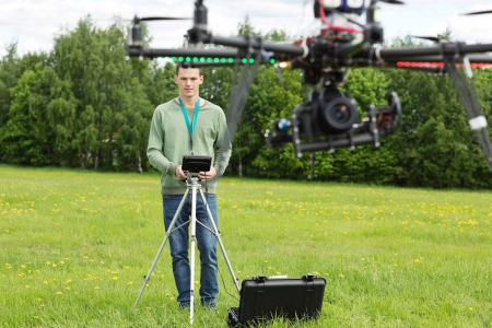 helicopter pilot: Young technician flying UAV photography helicopter with remote control in park Stock Photo