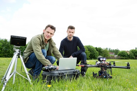 Portrait of young engineers using laptop by UAV helicopter and tripod at park photo
