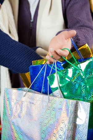 Cropped image of shopaholic couple carrying shopping bags at Christmas store photo