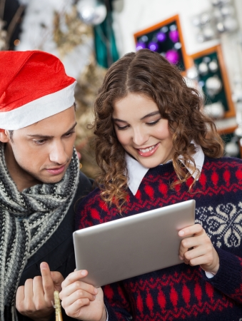 Young couple using digital tablet together at Christmas store photo