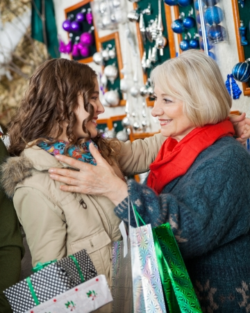 Affectionate mother and daughter with Christmas presents and shopping bags embracing at store photo