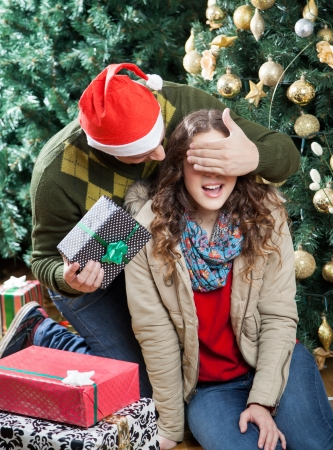 Young man in Santa hat surprising woman with Christmas presents in store photo
