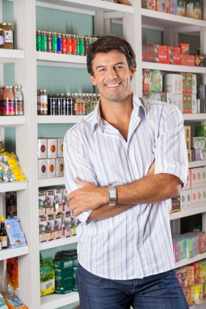 Portrait of confident mid adult man with arms crossed standing against shelves in grocery store photo