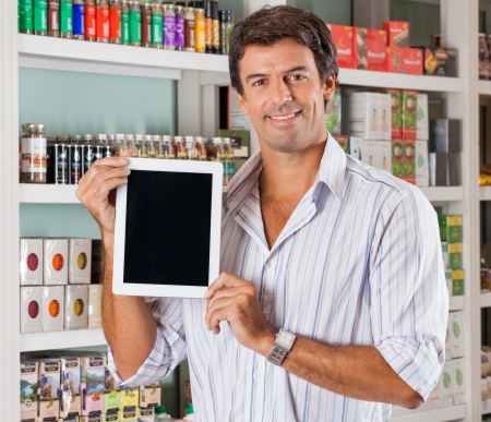 Portrait of happy mid adult man showing digital tablet in grocery store photo