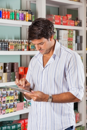 Mid adult man using digital tablet in grocery store photo