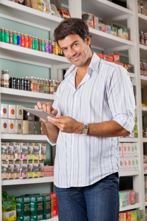Portrait of mid adult male customer with digital tablet in grocery store photo