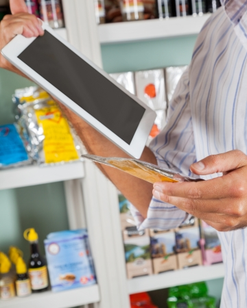 Midsection of male customer with digital tablet and product in supermarket photo