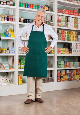 store display: Full length portrait of happy senior male owner standing with hands on hips in supermarket