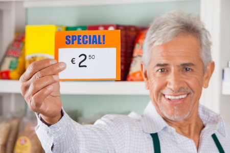 Portrait of happy senior male owner showing discount sign in grocery store photo