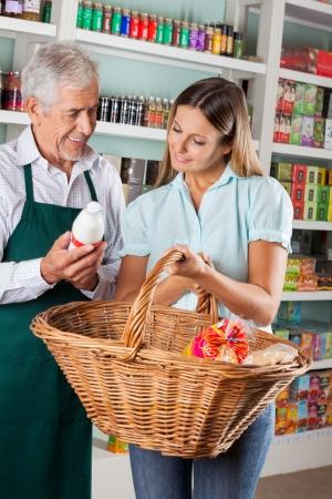 self help: Senior salesman assisting female customer buying groceries in supermarket