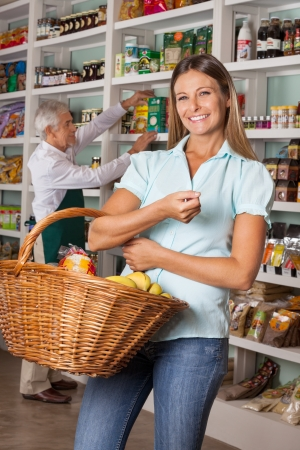 Portrait of mid adult woman holding shopping basket with salesman  photo
