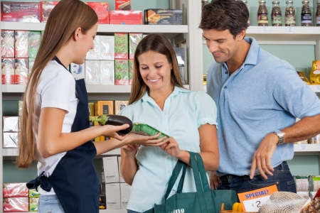 grocery basket: Saleswoman assisting couple in buying groceries at supermarket Stock Photo