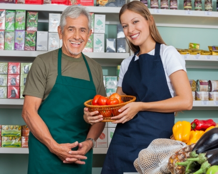 Portrait of saleswoman holding vegetable basket with male colleague in grocery store photo