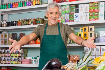 aprons: Senior salesman with arms outstretched in supermarket