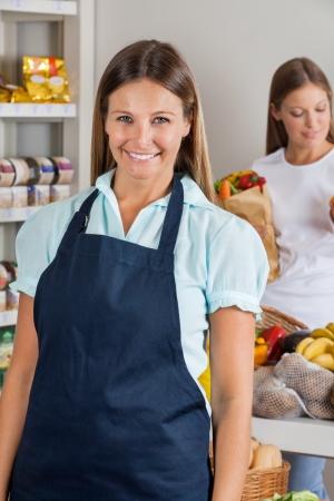 retailer: Portrait of confident saleswoman with female customer