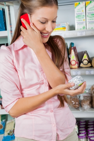 Young woman using mobile phone while looking at product in supermarket photo