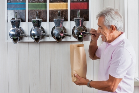 vending machine: Side view of senior man buying coffee beans from vending machine at grocery store Stock Photo