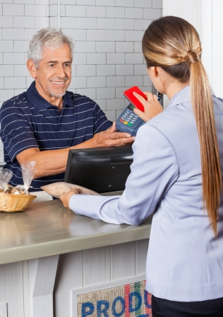 Senior salesman holding electronic reader while female customer paying through cellphone photo