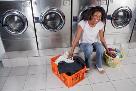 lavadora con ropa: Retrato de joven mujer afroamericana con cestas de ropa sucia que se sienta contra las lavadoras Foto de archivo