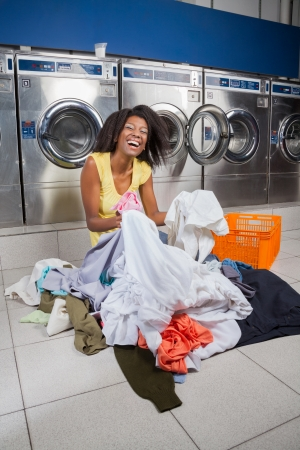 laundry pile: Happy young African American woman sitting with clothes on floor at laundry