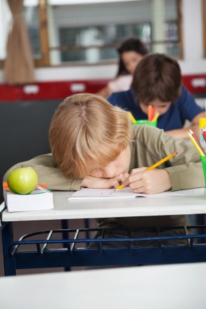 Tired schoolboy sleeping at desk in classroom photo