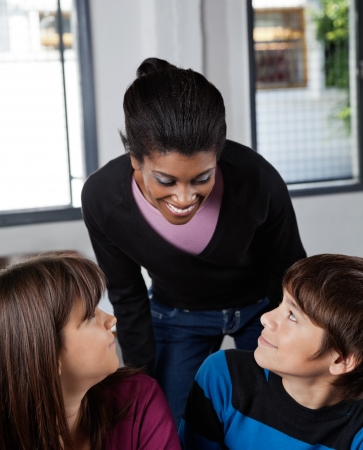 Young female teacher and schoolchildren looking at each other in classroom photo