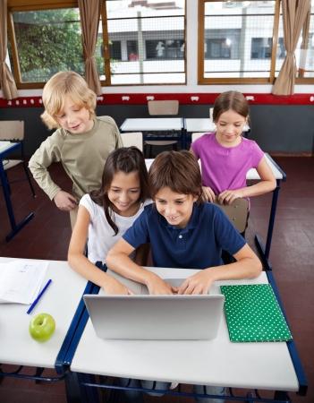 escuela primaria: Vista de ángulo alto de los pequeños escolares usando la computadora portátil en el escritorio en el aula