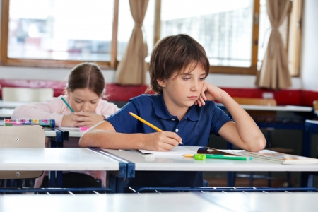Little boy looking away while writing in book with classmate studying at classroom Imagens