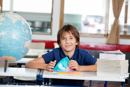 Portrait of cute little schoolboy sitting with books and globe at desk in classroom photo