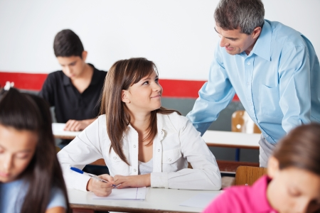 Mature male professor and schoolgirl looking at each other during examination in classroom photo