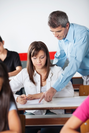 Mature male teacher assisting female student at desk in classroom photo