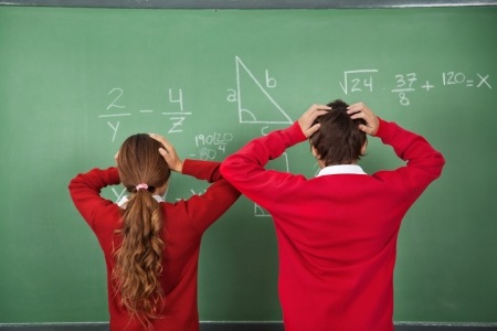 Rear view of confused schoolchildren standing against board in classroom photo