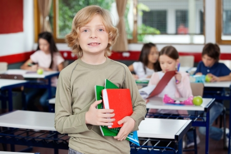 Portrait of little schoolboy holding books with classmates studying photo