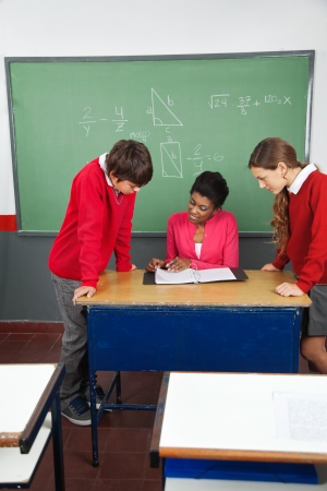 Young female teacher teaching teenage students at desk in classroom Stock Photo - 23745174