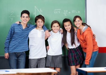 high class: Portrait of happy teenage friends standing together against board in classroom